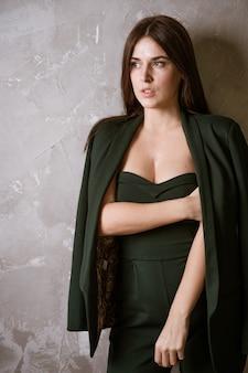 Schöne sexy frau im grünen anzug, der die kamera betrachtet