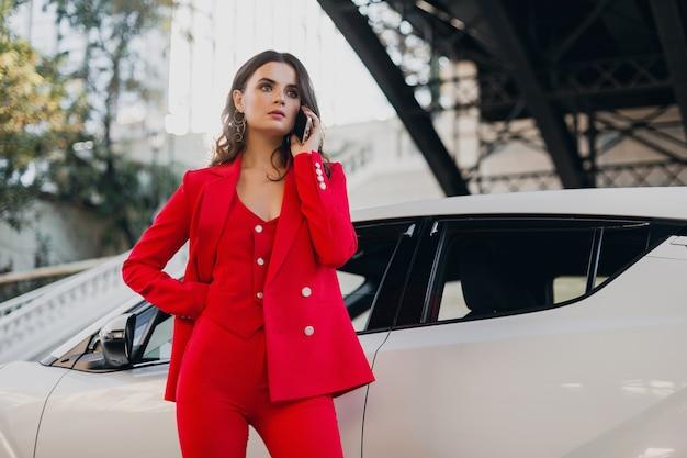 Schöne sexy frau im roten anzug posiert am auto, das auf geschäft am telefon spricht