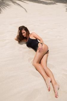 Schöne sexy frau im schwarzen bikini liegt auf dem weißen sand am strand