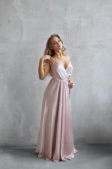 Schöne sexy frau in einem hellbeigen seidenkleid. lärm, unscharf