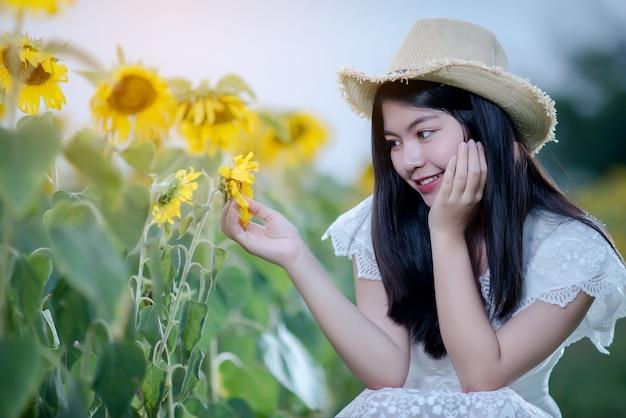 Schöne sexy frau in einem weißen kleid auf einem feld von sonnenblumen, gesunder lebensstil