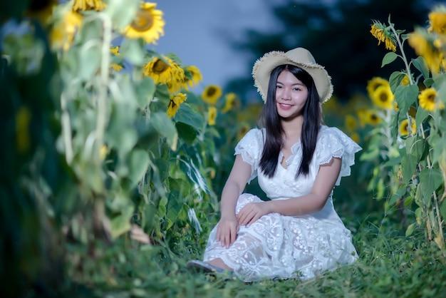 Schöne sexy frau in einem weißen kleid zu fuß auf einem feld von sonnenblumen