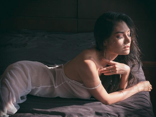 Schöne sexy frau mit der wäsche, die im raum sitzt