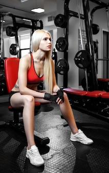 Schöne sexy frau mit perfekten bauchmuskeln im fitnessstudio