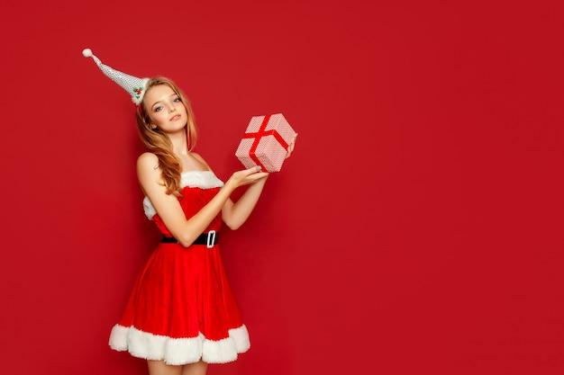Schöne sexy frau mit santa claus-kostüm und -geschenk