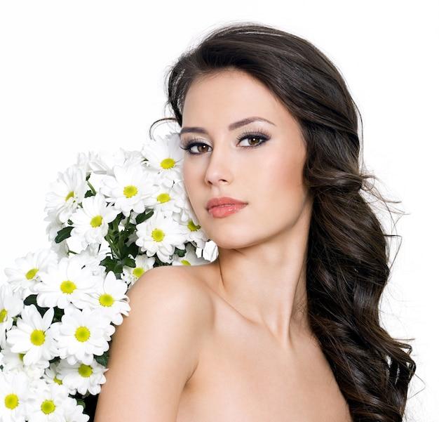 Schöne sexy frau und weiße blumen nahe ihrem körper - weißer hintergrund
