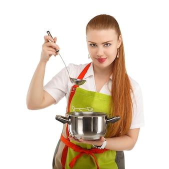 Schöne sexy junge frau, die frische mahlzeit lokalisiert auf weiß kocht