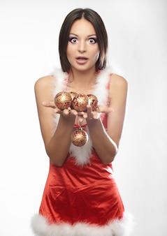 Schöne sexy junge frau, die weihnachtsmannkleidung mit spielzeug trägt