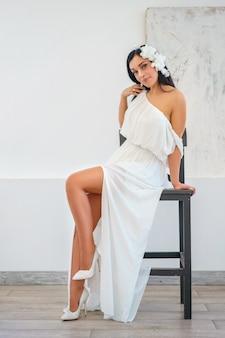 Schöne sexy junge frau im weißen kleid, das die aufstellung auf stuhl sitzt.