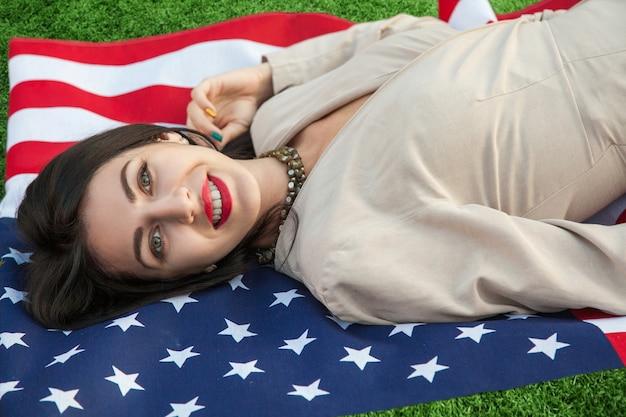 Schöne sexy junge frau mit klassischem kleid auf der amerikanischen flagge im park-mode-modell liegend