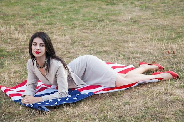 Schöne sexy junge frau mit klassischem kleid, das sich auf amerikanische flagge im park hinlegt. mode-modell hält uns lächelnd und blick in die kamera. usa-lifestyle mit einem zahnigen lächeln.