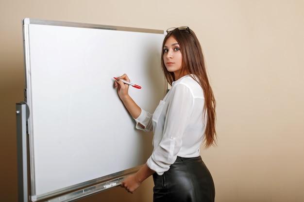 Schöne sexy junge frau schreibt auf das whiteboard leerer raum