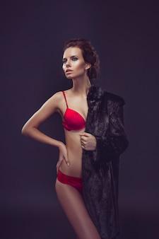Schöne sexy langhaarige brünette frau in roten dessous und pelzmantel posiert