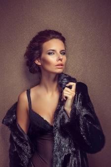 Schöne sexy langhaarige brünette frau in schwarzen dessous und pelzmantel posiert
