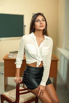 Schöne sexy lehrerin sitzt auf einem stuhl vor dem hintergrund des klassenzimmers
