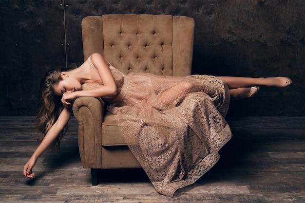 Schöne sexy modellfrau im glänzenden spitzenabendkleid, das im stuhl der beige farbe sitzend aufwirft Kostenlose Fotos