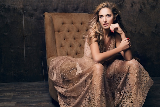 Schöne sexy modellfrau im glänzenden spitzenabendkleid, das im stuhl der beige farbe sitzend aufwirft