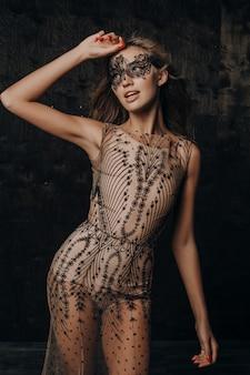 Schöne sexy modellfrau im luxus-spitzenabendkleid, das in der karnevalsmaske aufwirft