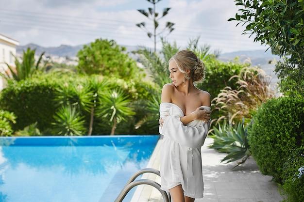 Schöne, sexy, modische blonde frau im peignoir, das nahe schwimmbad aufwirft