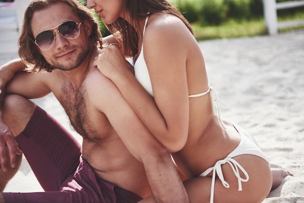 Schöne sexy paar kerl und mädchen tragen badebekleidung, wenn am strand. romantisch im sand liegen.