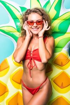 Schöne sexy perfekte frau in der sonnenbrille, die im roten bikini hält mit ananasmatratze lokalisiert auf grüner wand trägt
