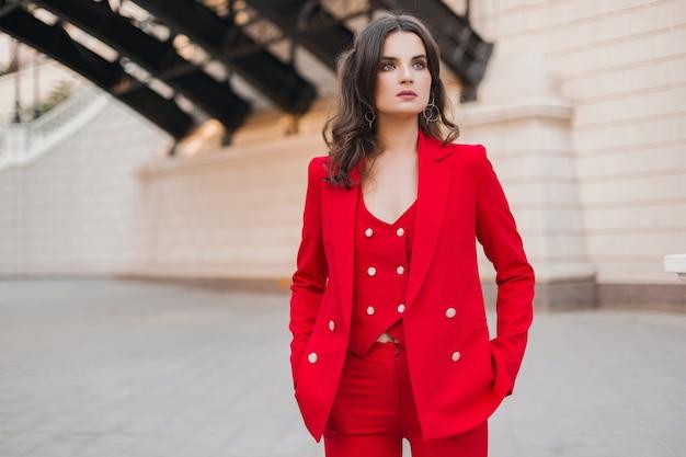Schöne sexy reiche geschäftsartfrau im roten anzug, der in stadtstraße, frühlingssommer-modetrend geht