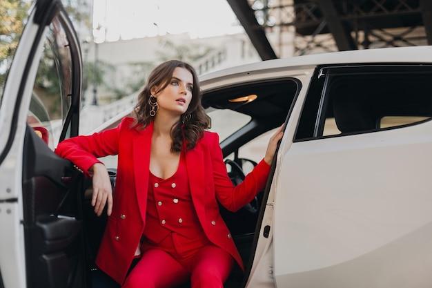 Schöne sexy reiche geschäftsfrau im roten anzug, der im weißen auto aufwirft