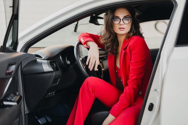 Schöne sexy reiche geschäftsfrau im roten anzug, der im weißen auto sitzt und brille trägt