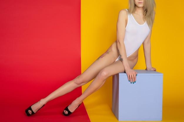 Schöne sexy schlanke frau mit perfektem körper im weißen body auf dem hintergrund posiert