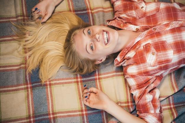 Schöne sinnliche blondine. mädchen, das am sonnigen herbsttag in herbstkleidung trägt. glückliche junge frau, die spaß mit blattfall hat. süße junge frau, die mit blättern spielt, sieht sehr sinnlich aus. herbst-konzept.