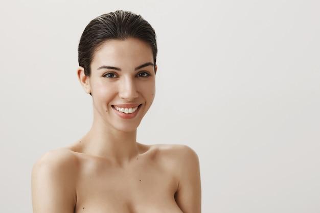 Schöne sinnliche brünette, die nackt steht und sorglos lächelt
