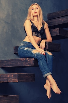 Schöne sinnliche erwachsene frau in einem bh und in jeans, die auf einer hölzernen freitragenden treppe aufwerfen. blick auf die kamera. persönliches wachstumskonzept