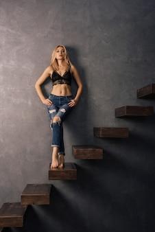 Schöne sinnliche frau in einem bh und in jeans, die auf hölzernen auslegerstufen stehen