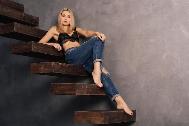 Schöne sinnliche frau in einem bh und jeans entspannt sich auf einer hölzernen auslegerstufe