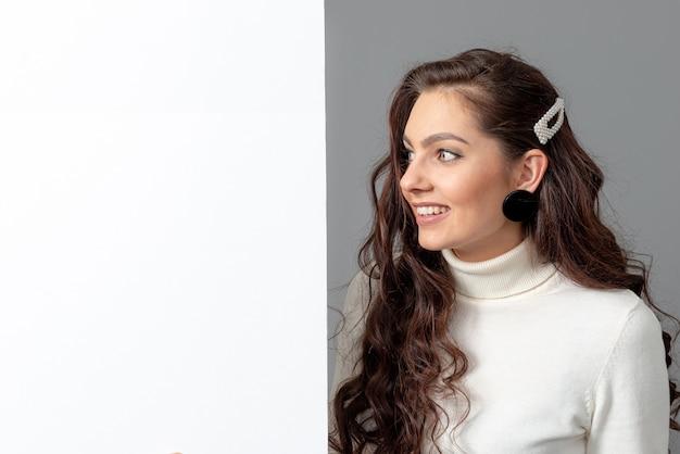 Schöne sinnliche geschäftsfrau mit langen lockigen haaren zeigt eine leere bilboard, isoliert auf grauem, kopierraum