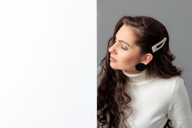 Schöne sinnliche geschäftsfrau mit langen lockigen haaren zeigt eine leere plakatwand, isoliert auf grau, kopienraum