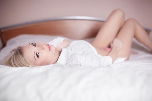 Schöne sinnliche sexy junge blonde frau, die nackt im bett liegt