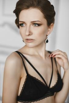 Schöne, sinnliche und modische junge frau in schwarzen dessous und ohrringen