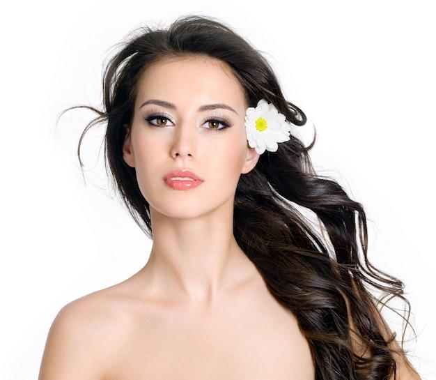 Schöne sinnlichkeitsglamourfrau mit sauberer haut und blumen in ihrem langen haar - weißer hintergrund