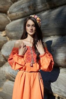 Schöne slawische frau in orange ethnischem kleid und kranzblumen auf kopf. schönes natürliches make-up. porträt eines russischen mädchens