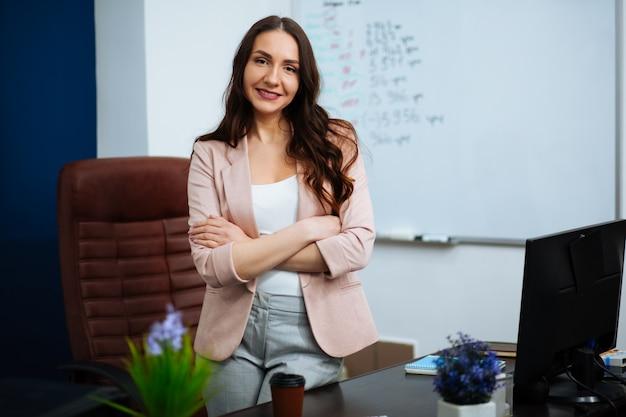 Schöne smarte süße charmante attraktive elegante besitzerin eines großen unternehmens hat ein online-meeting mit internationalen geschäftspartnern, sie sitzt an einem schreibtisch am arbeitsplatz