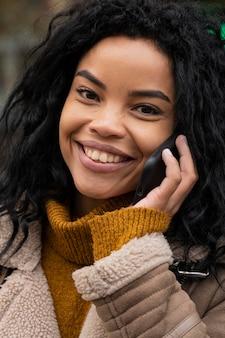 Schöne smiley-frau, die am telefon spricht