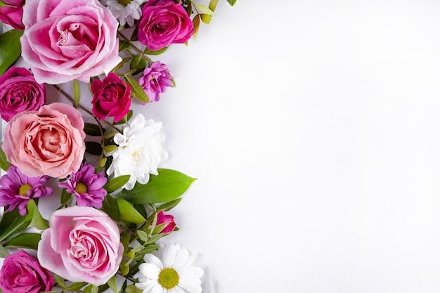 Schöne sommerblumen auf dem weißen hintergrund mit leerem raum für textrosa-rosen und weiß