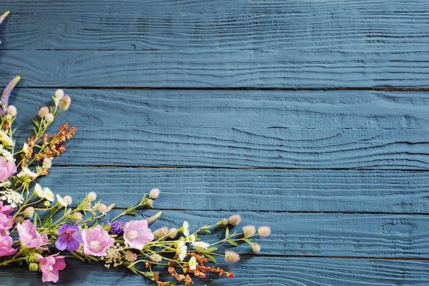 Schöne sommerblumen auf dunkelblauem hölzernem hintergrund