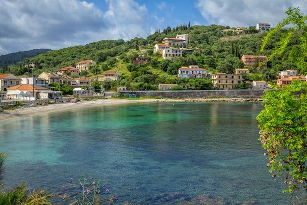 Schöne sommerlandschaft des resorts mit türkisfarbenem meerwasser, dorf mit bunten häusern und bergen am horizont und blauem himmel. korfu-insel, griechenland.