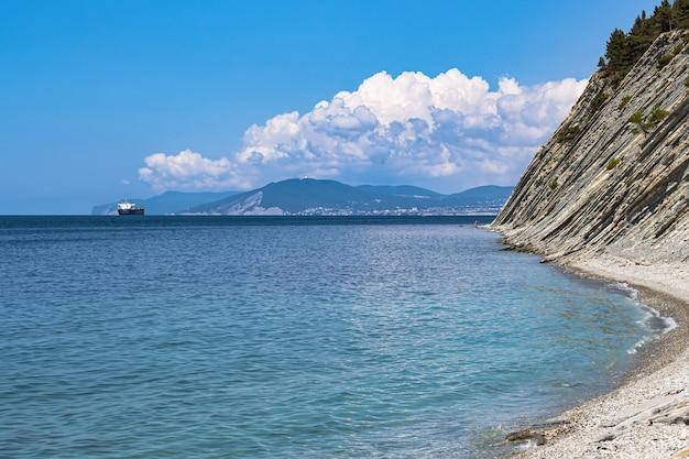 Schöne sommerlandschaft, strahlend blauer himmel mit wolken, steile klippen mit bäumen, wilder steinstrand und blick auf die stadt novorossiysk am horizont. russland, gelendschik, schwarzmeerküste