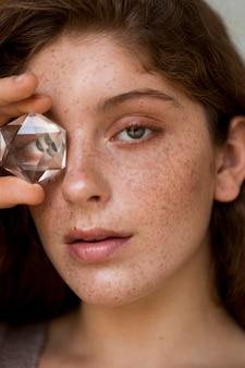 Schöne sommersprossige frau, die ein auge mit kristall bedeckt