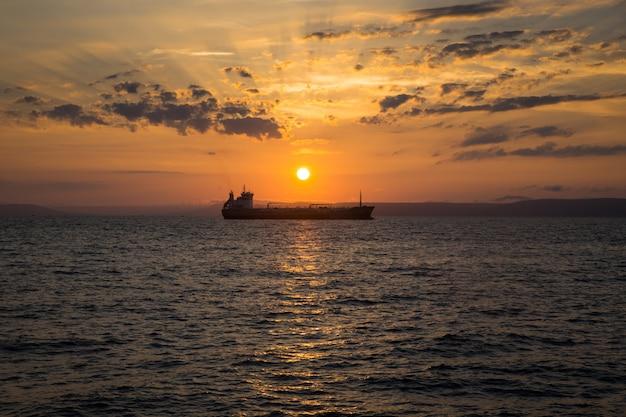 Schöne sonnenuntergangansicht über das see- und schiffsschattenbild in der mitte