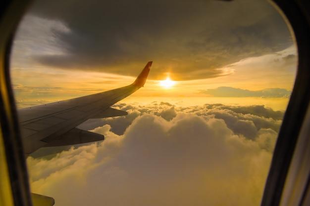 Schöne sonnenunterganghimmelwolken, die durch das flugzeugfenster sehen.