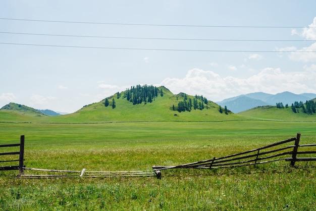 Schöne sonnige landschaft mit grünem waldberg und großem feld hinter gebrochenem altem holzzaun.